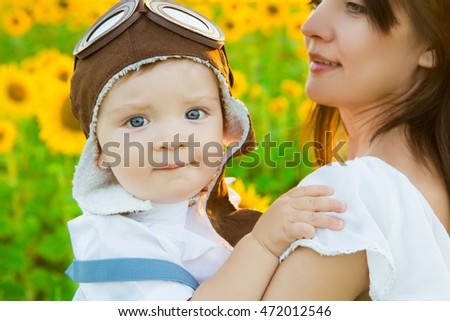 Boy and woman playing in aviator hat in the garden. Travel and vacation concept.