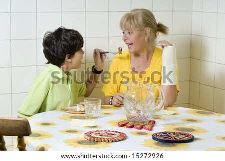 Boy and woman sitting at table. Boy feeding woman. Woman wearing cast. Horizontally framed photo.
