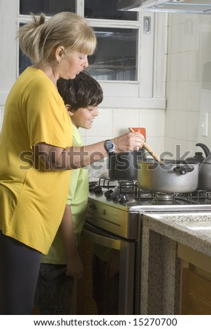 Boy and woman standing next to stove. Boy watching woman cook on stove. Vertically framed photo. - stock photo