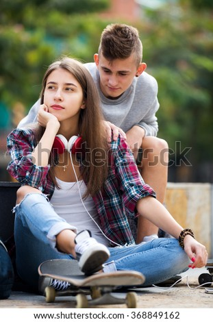 Boy apologizes to her girl after an argument outdoor. Focus on the girl - stock photo