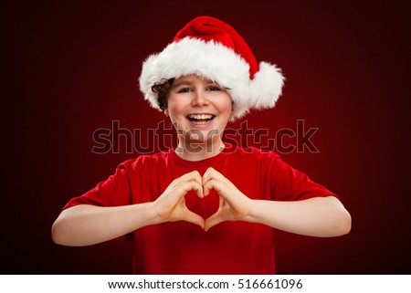 Boy as Santa Claus showing heart shape