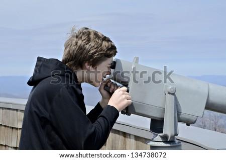 Boy at overlook at Brasstown Bald enjoying the scenery through a telescope. - stock photo