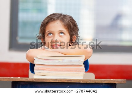 Boy at school happy thinking leaning on his books. - stock photo