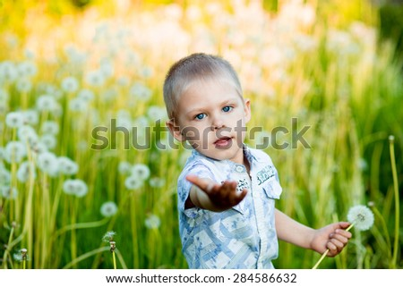 boy at sunset in the field reaches out forward - stock photo