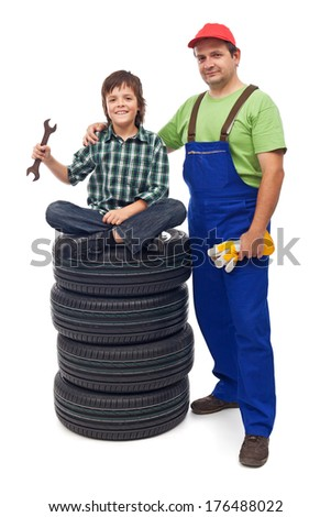 Boy at the auto repair shop with his father - sitting on new car tires, isolated - stock photo