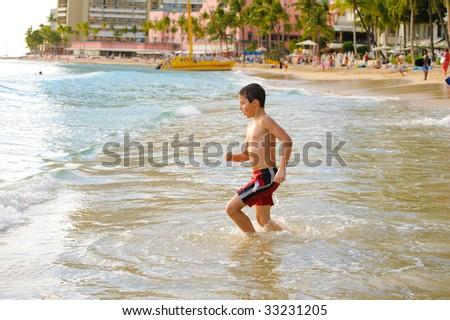 Boy at Waikiki beach - stock photo