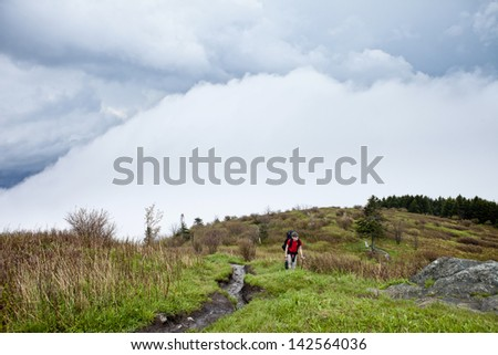 boy backpacking on mountain with approaching storm - stock photo