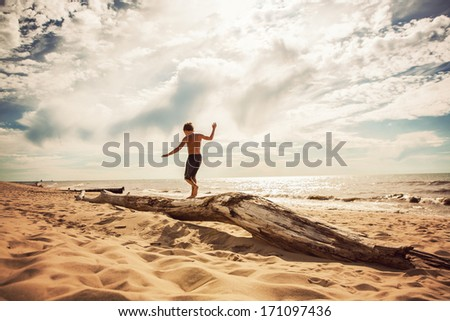 Boy Balancing on a washed up tree trunk on the beach  - stock photo