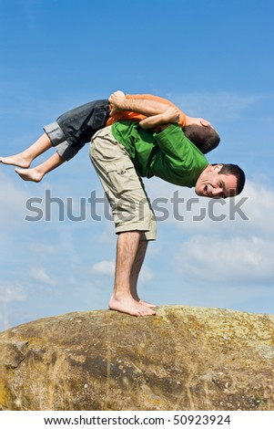 Boy balancing on his father's back