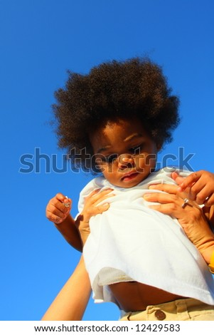 Boy being held up high - stock photo