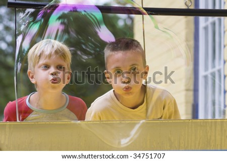 Boy blowing bubbles at discovery center - stock photo