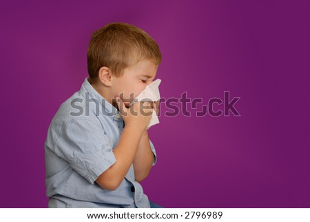 Boy blowing his nose - stock photo