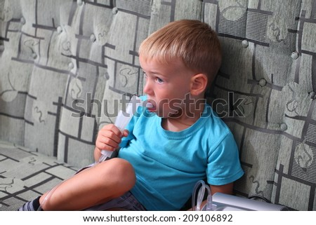 boy breathes through inhaler.5 years boy in a mask for breathing inhalation medication - stock photo