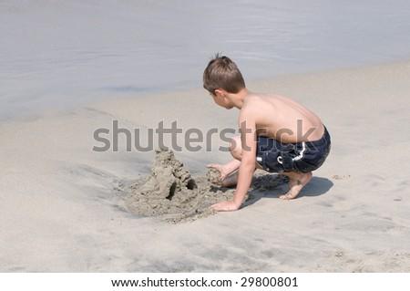 Boy building a sand castle - stock photo