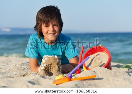 Boy building sand castles on the sea shore decorating them with shells - stock photo