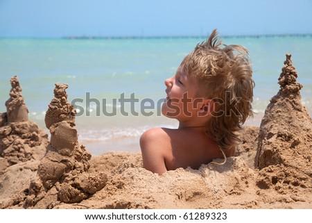 boy buried in sand on the sea beach - stock photo