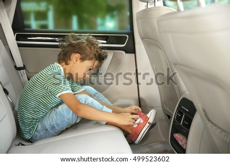Boy buttoning shoes in car