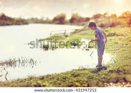 Boy by a river with a fishing net catching fish in the summer sun concept for childhood, healthy lifestyle and vacation - stock photo