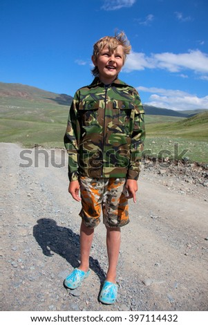 Boy camouflage outdoors in the mountains - stock photo