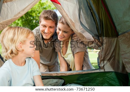 Boy camping with his parents - stock photo