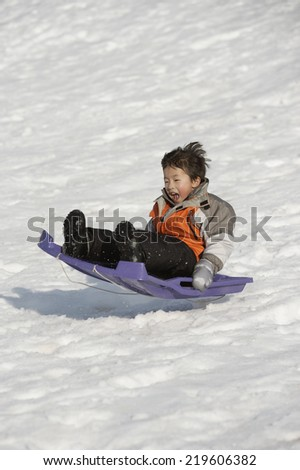 Boy catching air on sled - stock photo
