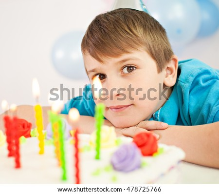 Boy celebrating birthday making a wish