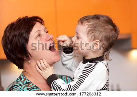 Boy checks the teeth of her grandmother - stock photo