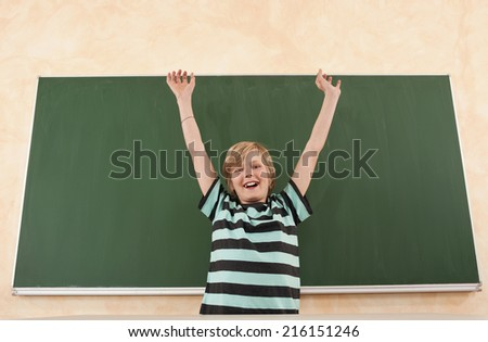Boy cheering in front of chalkboard