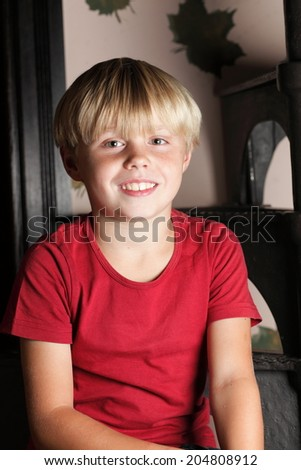 boy child kid in red sitting on stairs, playing indoor. Happy childhood - stock photo