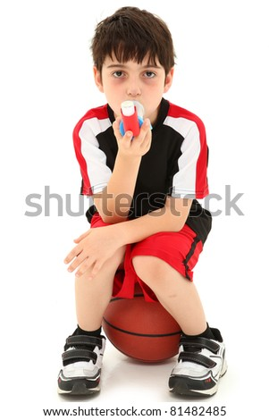 Boy Child with exercise or sport induced asthma attack sitting on basketball over white. - stock photo