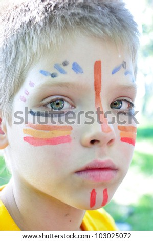 boy child with football fan paintings on face - stock photo