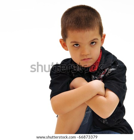 Boy, chin lowered, looking visibly upset with arms crossed over knee in front of white background, wearing jeans, a button up shirt and an earring. - stock photo