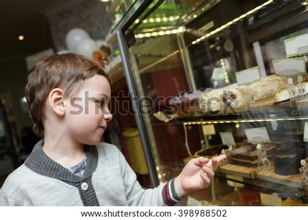 Boy choosing a cake in the cafe
