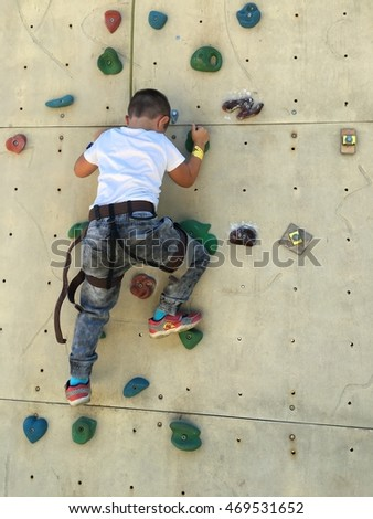 boy climb an artificial wall - bouldering