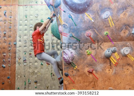 boy climbing on practical wall indoor, bouldering training - stock photo