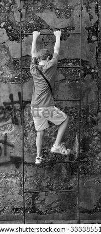 boy climbing over missing rung in rusty ladder - stock photo