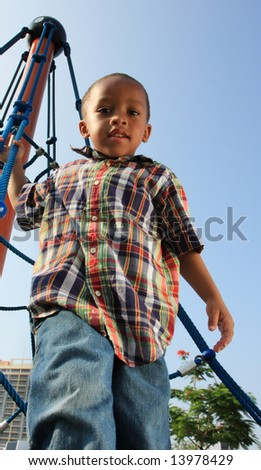 Boy Climbing Ropes at a Playground - stock photo