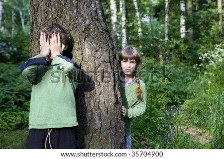 boy close his eyes by hand. Girl look out tree. Hide-and-seek - stock photo