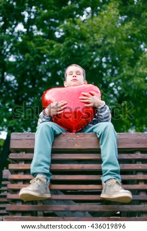 boy closed his eyes hugging a big red heart. teenage love concept. the view from the bottom up - stock photo