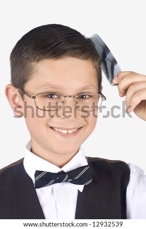 Boy combs the hair on a white background - stock photo