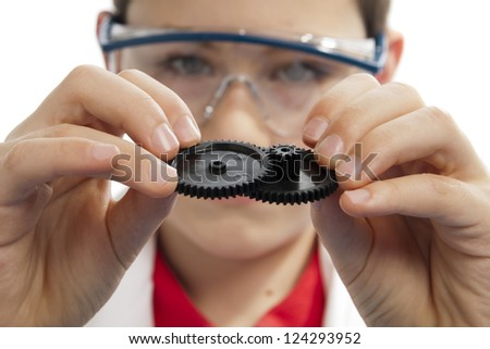 Boy connecting multiple gears while wearing safety glasses, side view - stock photo