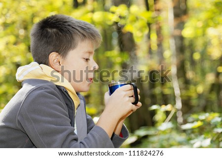 Boy cools hot tea while sitting in autumn forest - stock photo