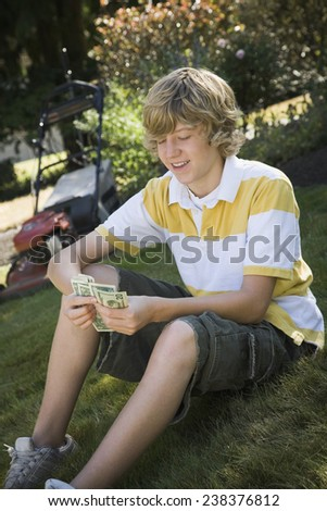 Boy Counting Money from Lawn Mowing Job - stock photo