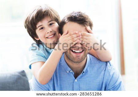 Boy covering father's eyes  - stock photo