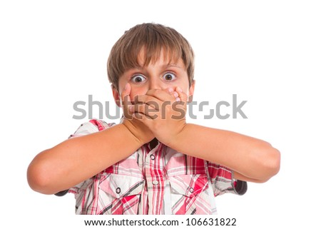Boy covering his mouth and looking very shocked - stock photo