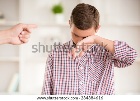 Boy crying while father scold him. Family quarrel. - stock photo