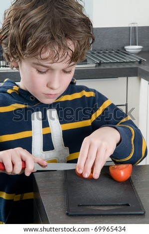 Boy cutting a tomato, getting ready to cook.