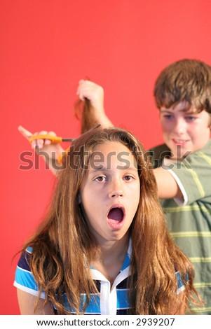 boy cutting girls hair scream vertical - stock photo