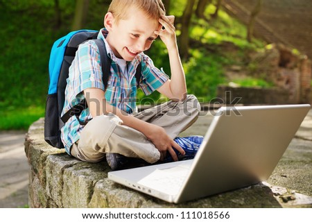 Boy delighted with notebook - stock photo
