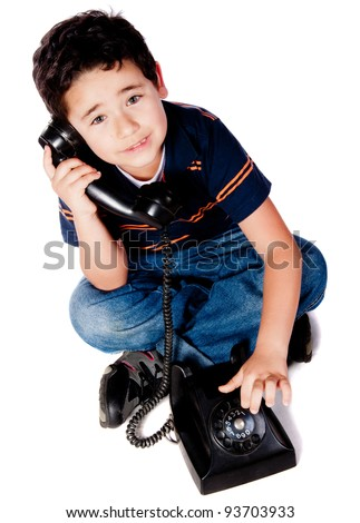 Boy dialing and talking on the phone - isolated over a white background